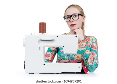 Young girl with glasses sews on a sewing machine, isolated on white background