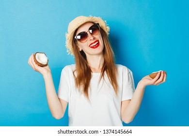 A young girl with glasses and a straw hat holding a coconut, blue background. Concept vacation, tourist trip, summer and tropics, summertime.