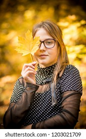 Young girl with glasses walks in the autumn forest