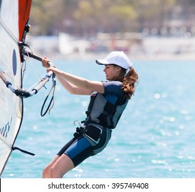young girl glides on windsurfing in sea