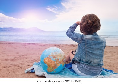 A Young girl with globe sits on the sand beach and looking at the sunset on sea