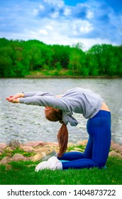 young girl goes in for sports in nature. healthy lifestyle.flaxible child doing joga poses bridge streching in the nature. Copy space