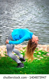 young girl goes in for sports in nature. healthy lifestyle.flaxible child doing joga poses bridge streching in the nature.Warm-up on the shore of a natural pond, river, lake, sea. Copy space