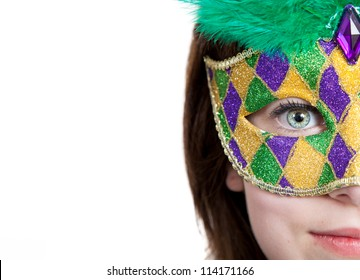 A young girl in a gold, purple and green mardi gras mask with copy space