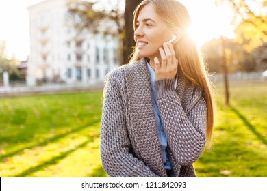Young girl, in a good mood, listening to music with wireless headphones, on an autumn day, enjoying the good weather.