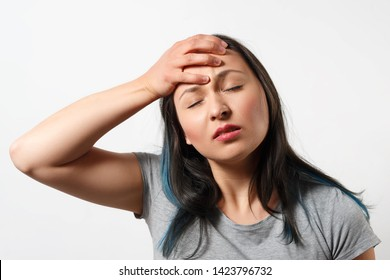 a young girl grabs her head with her hand and depicts a severe headache. On white background.