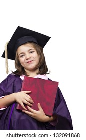 Young girl in graduation dress. Attractive 5 year old girl in large graduation cap and gown with diploma over white background