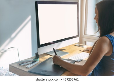 Young girl graphic designer using modern computer and graphic tablet with stylus while working at office, professional female designer sitting at modern workspace with wooden table, blurred background