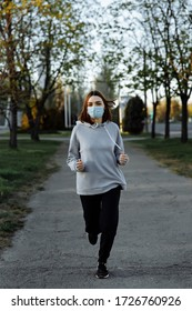 A young girl in a gray sweater runs down the street in a blue mask. Pandemic Sports