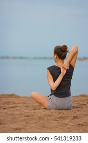 Young girl in a gray T-shirt and shorts is engaged in yoga on the beach one morning at dawn the sun. Meditation in nature. The concept of sports, fitness, healthy lifestyle