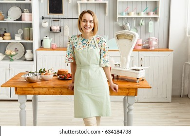 A young girl in a green apron smiles in the kitchen