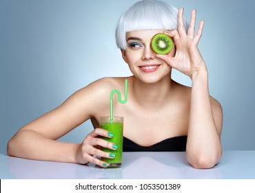 Young girl with green detox smoothie and a half of kiwi in front of her face on blue background. Skin care and beauty concept.
