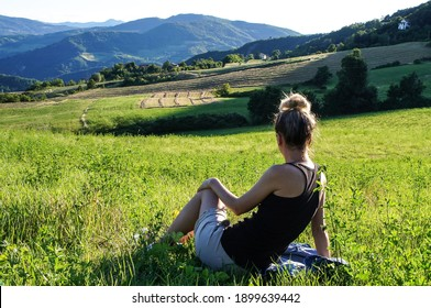 Young girl in the green meadow on the mountains background