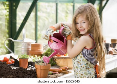Young girl in greenhouse putting plant in pot