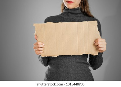 A young girl in a grey jacket holding a piece of cardboard. Prepared for your text.