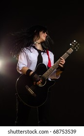 young girl with a guitar, on black background