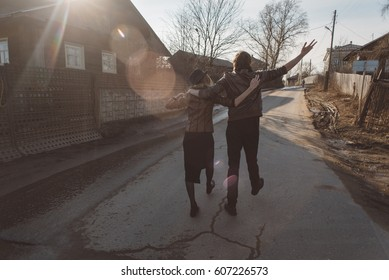 a young girl and a guy in a brown leather jacket running, jumping on the road in the village at sunset on a clear spring day, holding hands