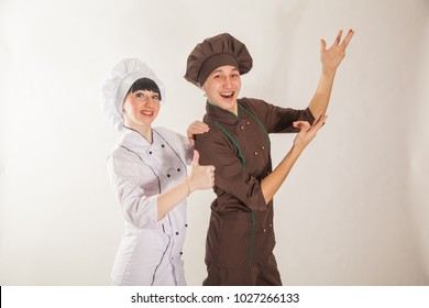 Young girl and guy dressed as cooks. Confectioners on a white background. Teamwork. The Chef
