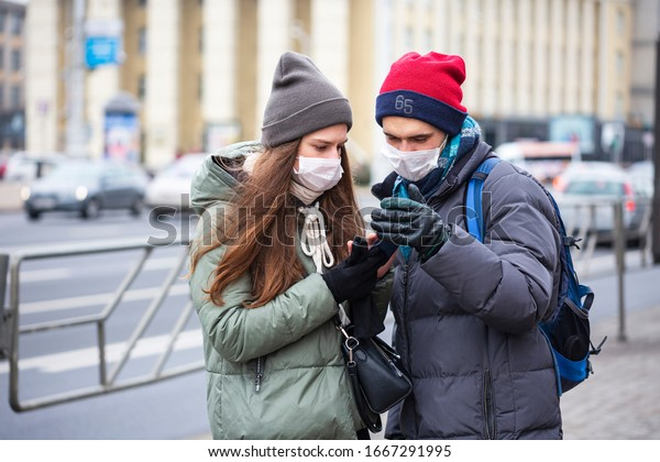 Young Girl and Young Guy on City Street in Protective Masks on His Face. looking at Phone. Concept - Prevent Coronavirus Infection. Europe. Casual. Closeup. Selective Focus.
