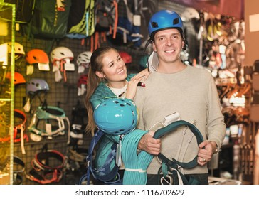 Young girl and guy in sports store choosing climbing equipment