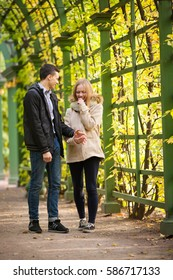 Young girl and a guy are walking through the Park, hugging and kissing. romantic mood.