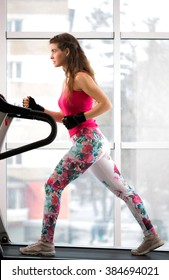 young girl in the gym on the treadmill