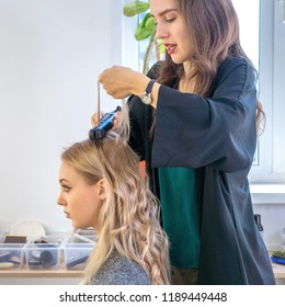 young girl hairdresser does hairdo for client blonde, square framing, warm toning