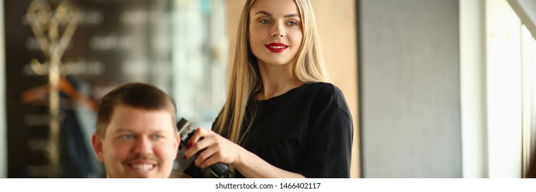 Young Girl Hairstylist Shave Smiling Male Client. Female Hairdresser Shaving Man with Electric Razor in Beauty Salon. Woman Barber Cutting Guy Customer in Barber Shop. Person Getting Haircut