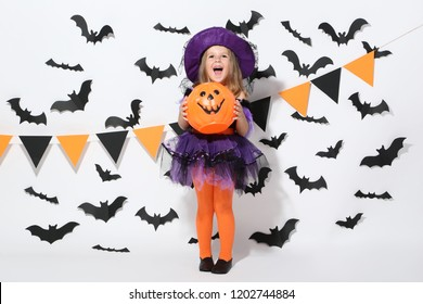 Young girl in halloween costume with pumpkin bucket on white background