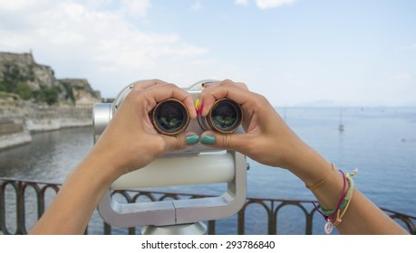 Young girl hands with colourful painted nails holding public binoculars with seaside view