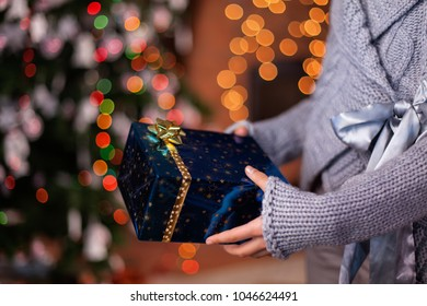 Young girl hands offering beautiful wrapped christmas present - closeup with colorful lights background