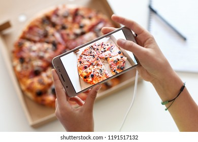 Young girl hands taking a picture of her meal - a box of appetizing fresh pizza with rich topping