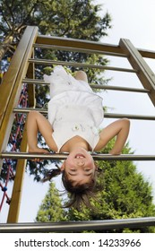 Young girl hanging on jungle gym at playground.