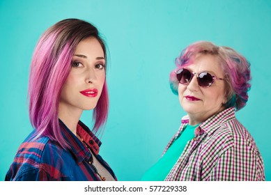 Young girl and happy senior woman in colorful casual clothes. Two generations of hipsters. Stylish senior woman on blue background. Common colorful hair and informal lifestyle of two generations
