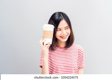 Young girl happy smile and cheerful in red dress hold a white coffee mug in hand. Concept summer travel.