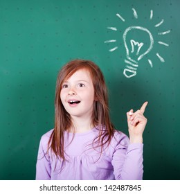 Young girl has a bright idea as she stands against the blackboard at school with a look of enlightenment and raises her finger pointing to a lightbulb on the board