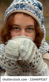 A young girl in a hat with Christmas patterns and a Cup in her hands on a street blurred background.