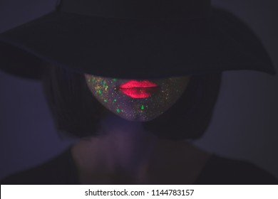 Young girl in hat with fluorescent paint on lips and face. Studio shot.