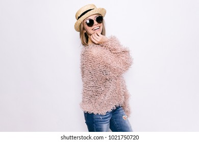 Young girl in a hat and glasses and a cardigan on a white background