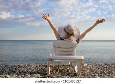 young girl in a hat lying on a sun lounger with her hands up, enjoys life, the view from the back.