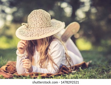 Young girl with hat lying on grass. Happy little girl hiding face under hat.