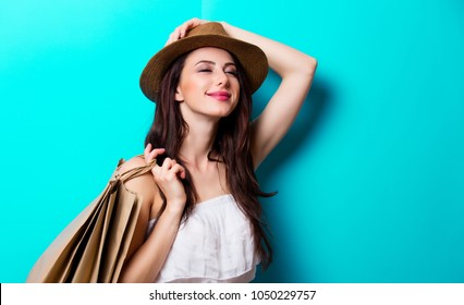 Young girl in hat with shopping bags on blue background