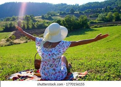Young girl in the hat with the spread arms under the sunlight in the middle of green meadow.
