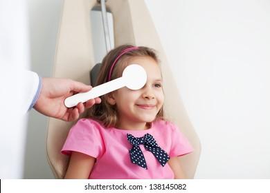 Young girl is having eye exam performed by optician, optometrist or eye doctor.