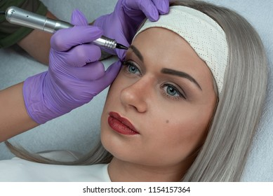 A young girl having eyeliner and eyebrows black, permanent makeup, micropigmentation.