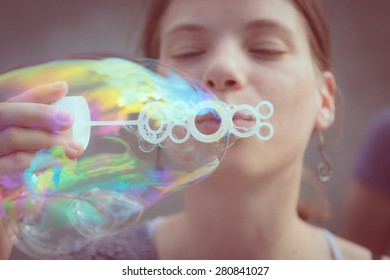 Young girl having fun and blowing bubbles.