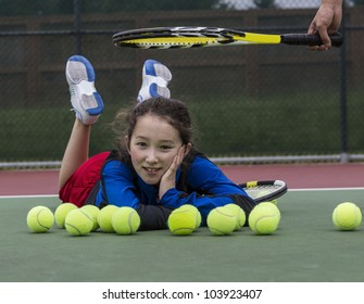 Young girl having fun on outdoor tennis courts with coach's racket above her head