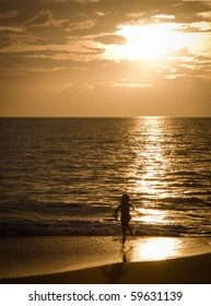 A young girl is having fun running on a sandy beach at sunset on beautiful Hawaii, Maui