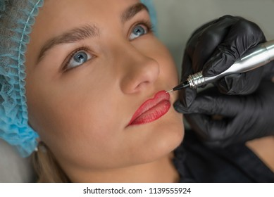 A young girl having red lips permanent makeup, micropigmentation.