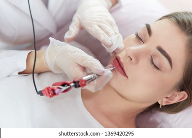 A young girl having red lips permanent makeup, micropigmentation